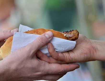 Image of hot dog being passed from one hand to another hand