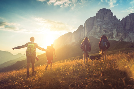 four teens hiking in mountains with sunlight